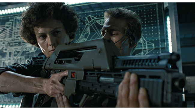 If it's OK to use a famous example, consider this. The weapon looms; the background is the display board. These are not chance happenings (from Aliens).jpg