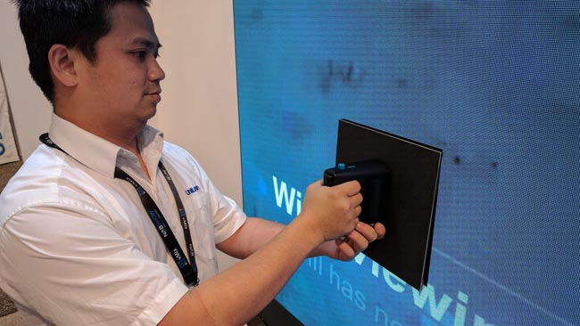 Unilumin technician demonstrating  the removable modules in the boardroom display.jpg